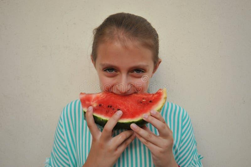 Conceito do verão com a moça que come uma melancia fotos de stock royalty free