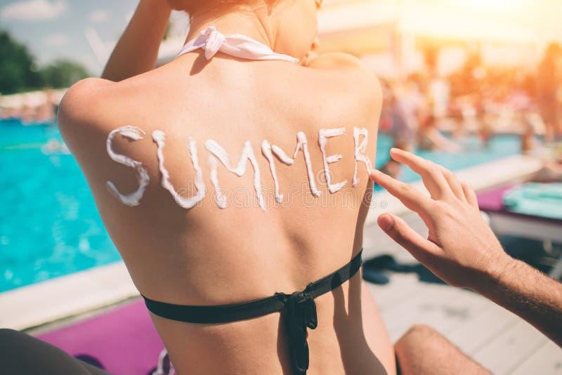 Conceito do verão Equipe a escrita do verão da palavra em uma parte traseira do ` s da mulher Equipe a aplicação da proteção sola imagens de stock royalty free