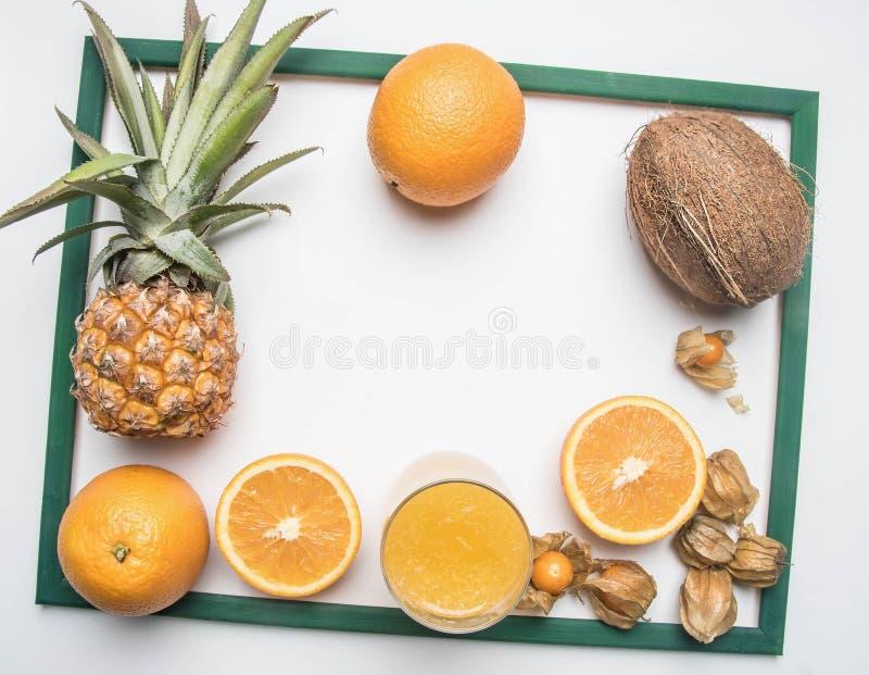 Conceito do verão, fruto saboroso fresco, abacaxi, laranjas, coco, suco de laranja, em um quadro verde, em um fundo rústico branc foto de stock royalty free