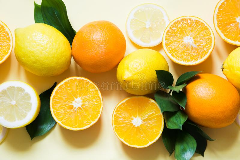 Conceito do verão O grupo de frutos tropicais, de limão, de laranja e de verde sae no amarelo Fim acima Vista superior foto de stock royalty free