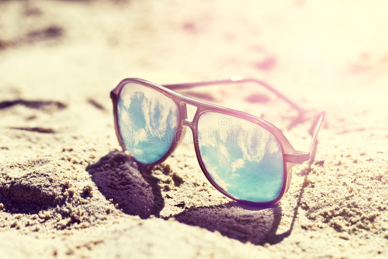 Conceito do verão ou das férias Óculos de sol bonitos na areia E fotos de stock