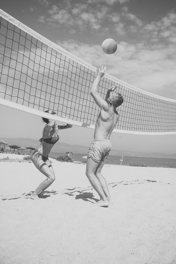 Conceito do voleibol de praia Os pares têm o divertimento que joga o voleibol Os pares ativos desportivos novos bateram fora da b imagens de stock