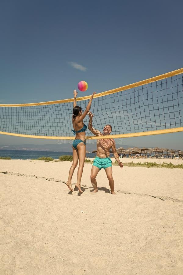 Conceito do voleibol de praia Os pares têm o divertimento que joga o voleibol Os pares ativos desportivos novos bateram fora da b imagem de stock