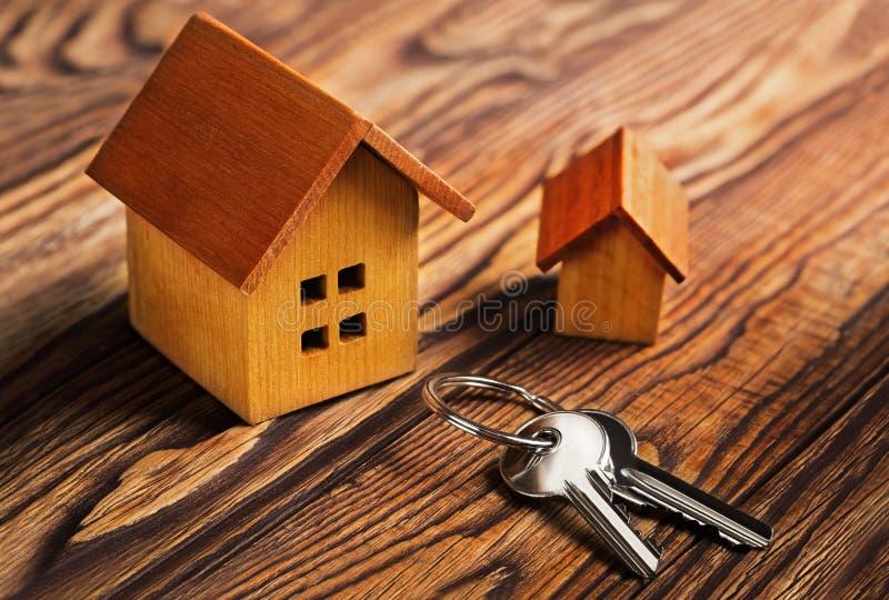 Conceito dos bens imobiliários com casa e chave no fundo de madeira Ideia para o conceito dos bens imobiliários, bens pessoais imagens de stock
