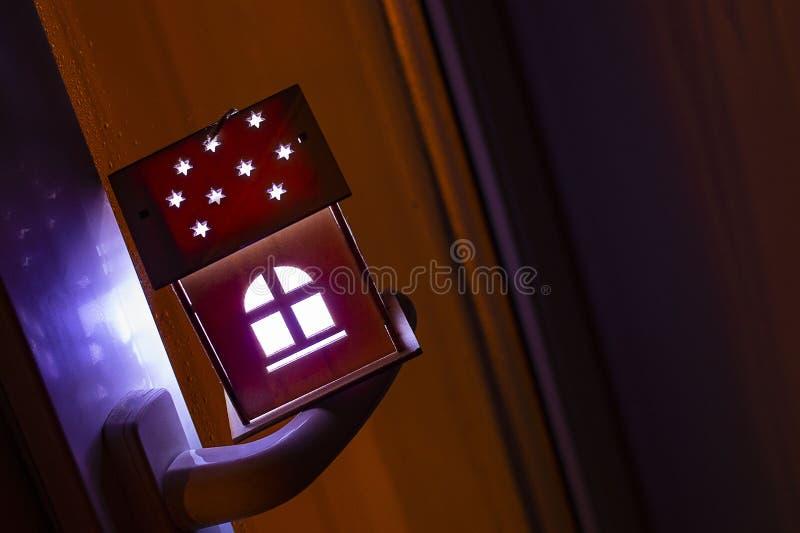 Conceito dos bens imobiliários com uma casa de madeira do brinquedo pequeno no punho de janela A ideia do conceito de bens imobil fotografia de stock royalty free