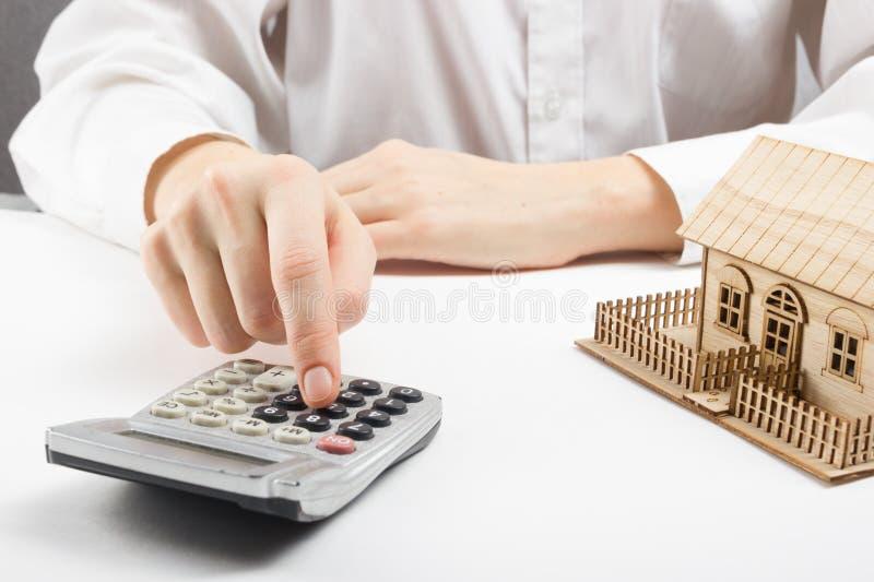 Conceito dos bens imobiliários - homem de negócios que conta atrás do modelo arquitetónico home imagens de stock