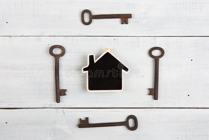 Conceito dos bens imobiliários - poucas casa e chaves na mesa de madeira branca imagem de stock royalty free