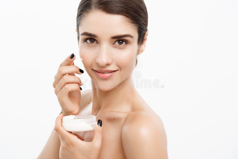 Conceito dos cuidados com a pele da juventude da beleza - retrato caucasiano bonito ascendente próximo da cara da mulher que apli imagem de stock