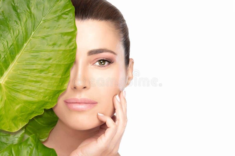 Conceito dos cuidados com a pele com uma mulher bonita nova que toca em sua cara atrás de uma folha Retrato da beleza dos termas imagem de stock