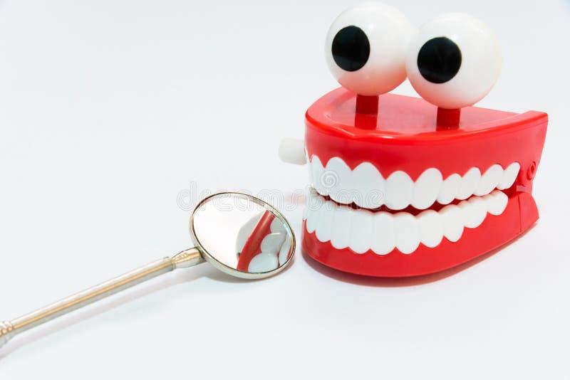 Conceito dos cuidados dentários no fundo branco com a ferramenta do dentista do espelho fotografia de stock royalty free