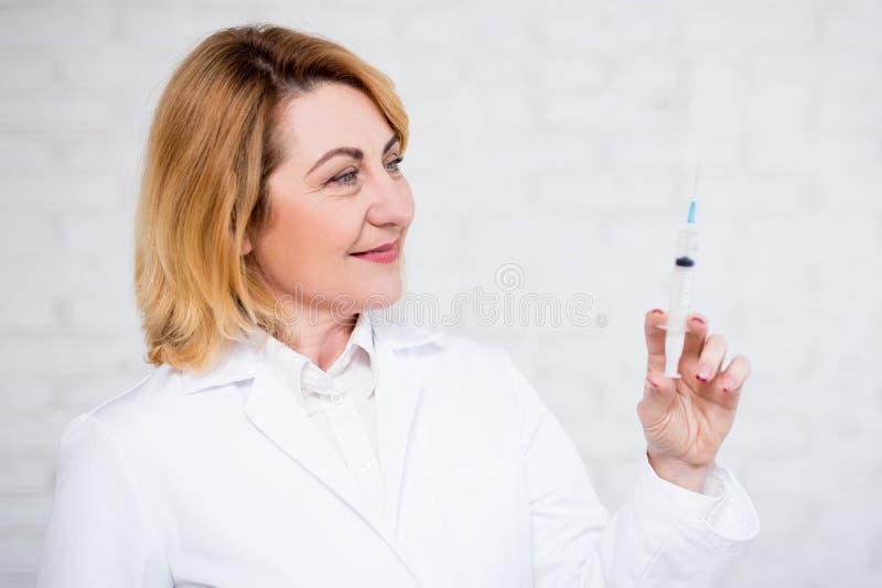 Conceito dos cuidados médicos, da vacinação e da cosmetologia - retrato do doutor fêmea maduro que guarda a seringa sobre a pared fotografia de stock