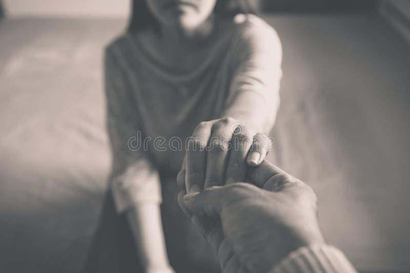 Conceito dos cuidados médicos de Meantal, homem que dá a mão a mulher deprimida foto de stock