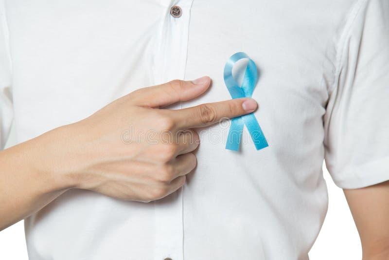Conceito dos cuidados médicos do ` s dos homens - próximo acima da mão masculina que aponta à luz - fita azul para o câncer da pr fotos de stock royalty free