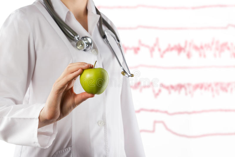 Conceito dos cuidados médicos e da medicina - a mão do doutor fêmea que guarda a maçã verde Feche acima do tiro no cinza fotografia de stock