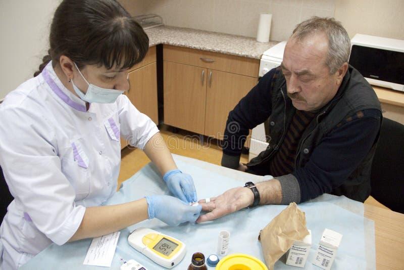 Conceito dos cuidados médicos, o idoso e o médico - doutor ou enfermeira fêmea com valor de medição do açúcar no sangue do pacien foto de stock