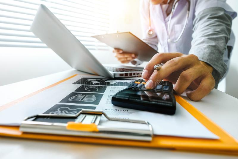 Conceito dos custos e das taxas dos cuidados médicos A mão do doutor esperto usou uma calculadora e uma tabuleta para médico foto de stock royalty free