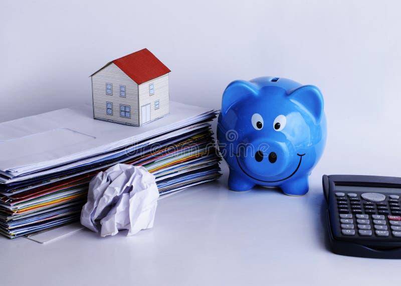 Conceito dos empréstimos hipotecários com a casa do mealheiro e do papel na conta p imagens de stock royalty free
