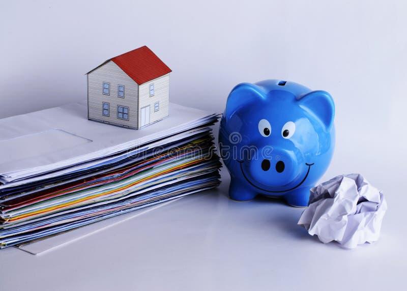 Conceito dos empréstimos hipotecários com a casa do mealheiro e do papel na conta p fotos de stock