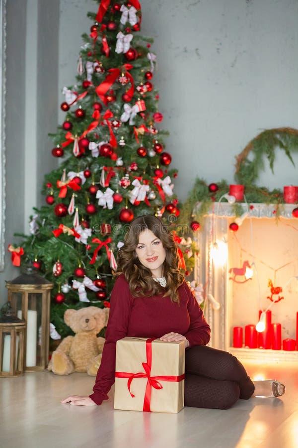 Conceito dos feriados, da celebração e dos povos - jovem mulher no vestido elegante sobre o fundo do interior do Natal Imagem com fotos de stock royalty free