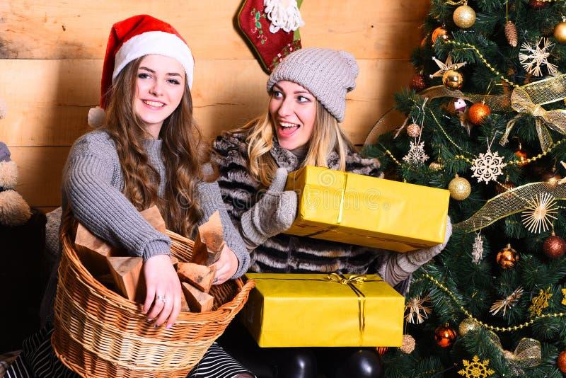 Conceito dos feriados de inverno As senhoras em chapéus de Santa guardam presentes amarelos fotografia de stock