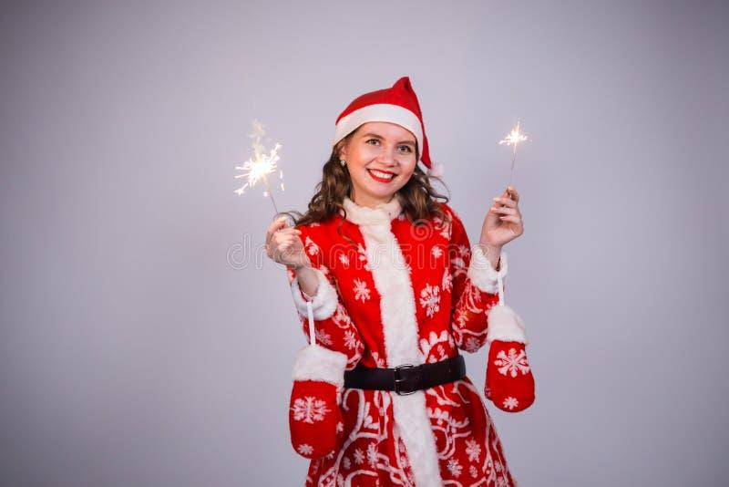 Conceito dos feriados, do partido e dos povos - mulher de sorriso do Natal que veste o terno de Papai Noel no fundo claro imagens de stock
