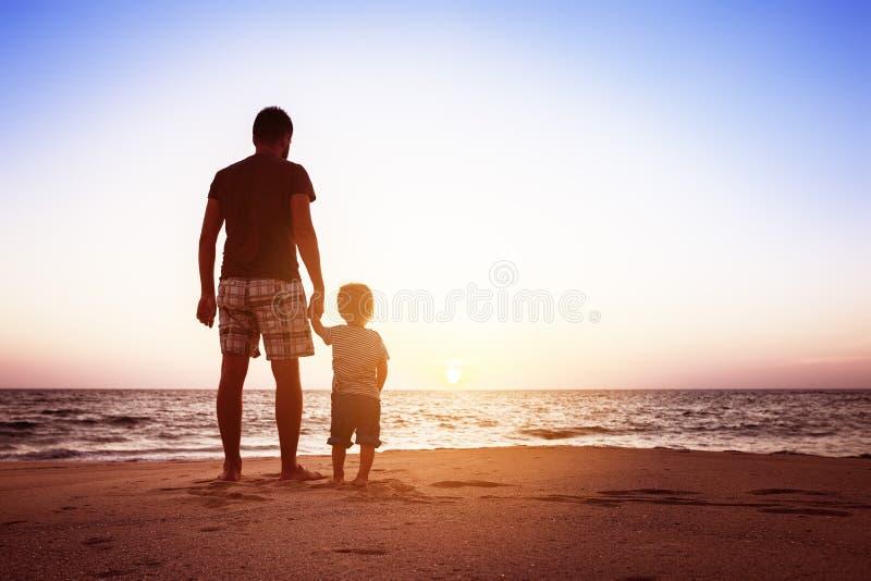 Conceito dos feriados do por do sol da praia do pai e do filho imagens de stock