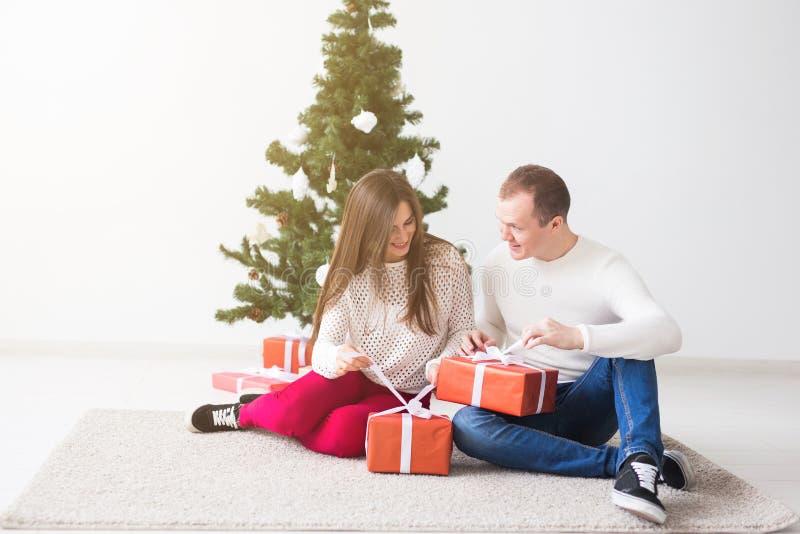 Conceito dos feriados e do Natal - presentes de abertura de sorriso do Natal dos pares novos modernos imagens de stock