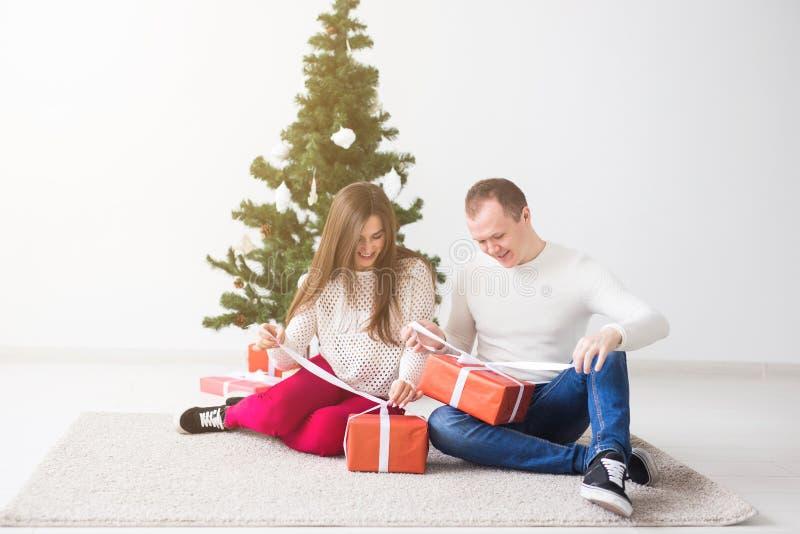 Conceito dos feriados e do Natal - presentes de abertura de sorriso do Natal dos pares novos modernos fotos de stock royalty free