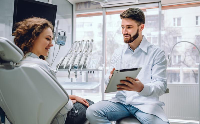 Conceito dos povos, da medicina, do stomatology e dos cuidados médicos - tablet pc masculino feliz da exibição do dentista ao pac fotos de stock