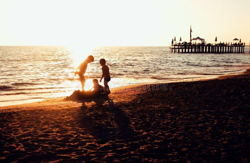 Conceito dos povos do estilo de vida: silhueta de três rapazes pequenos na praia do por do sol que joga na água fotografia de stock royalty free