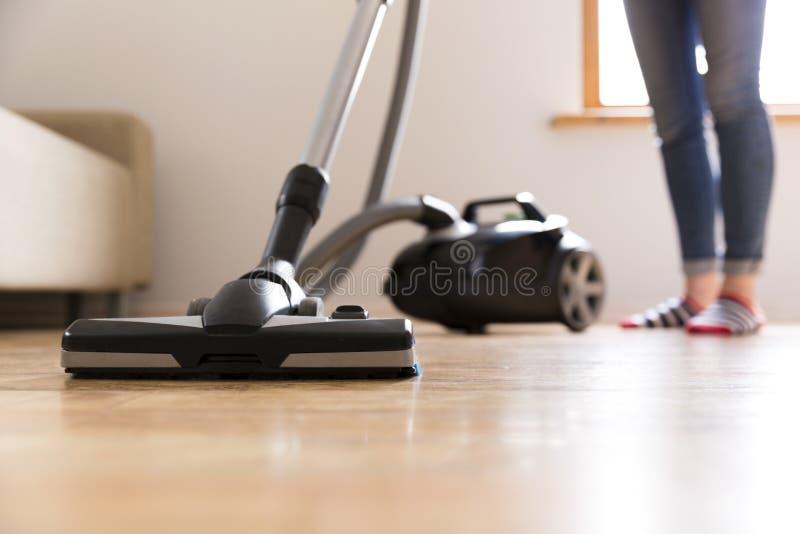 Conceito dos povos, dos trabalhos domésticos e das tarefas domésticas - mulher feliz com aspirador de p30 em casa Limpeza da prim fotografia de stock