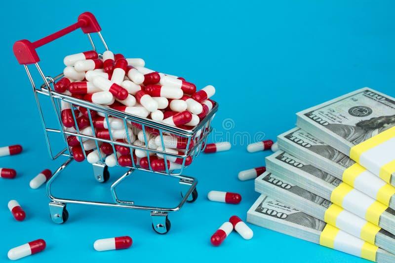 Conceito dos pre?os do medicamento de venda com receita O carrinho de compras encheu c?psulas medicinais vermelhas fotografia de stock