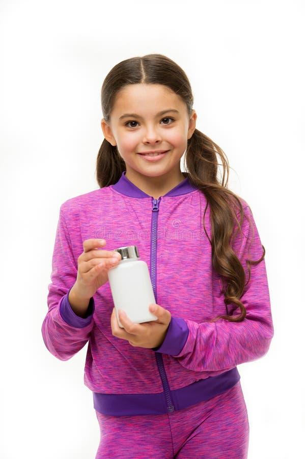 Conceito dos suplementos à vitamina Da posse longa do cabelo da menina a garrafa plástica com medicinas copia o espaço Adicione a imagem de stock