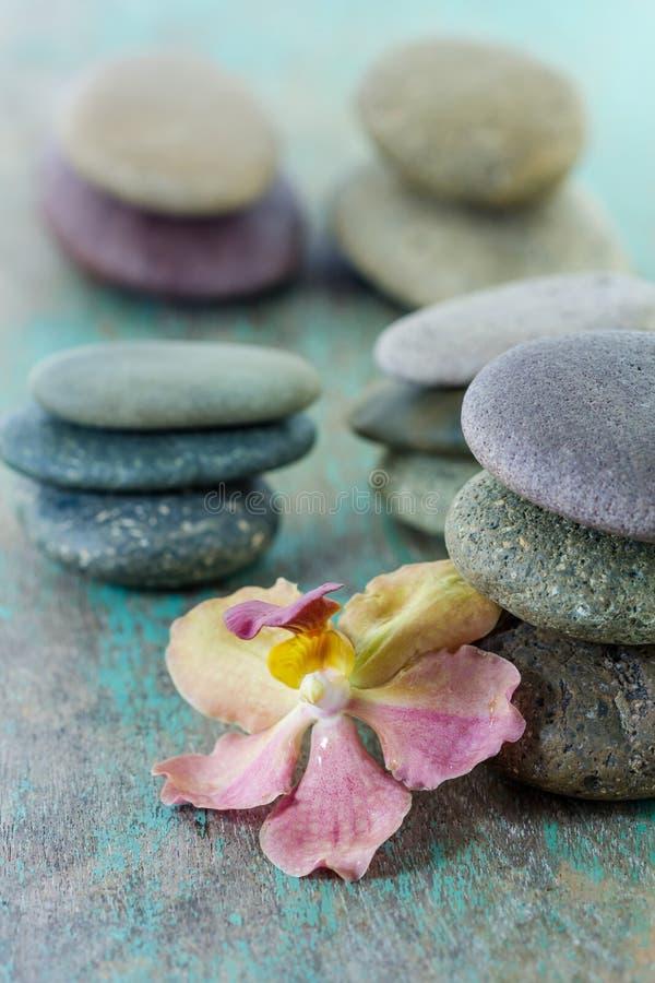 Conceito dos termas com pedras e orquídea do zen foto de stock