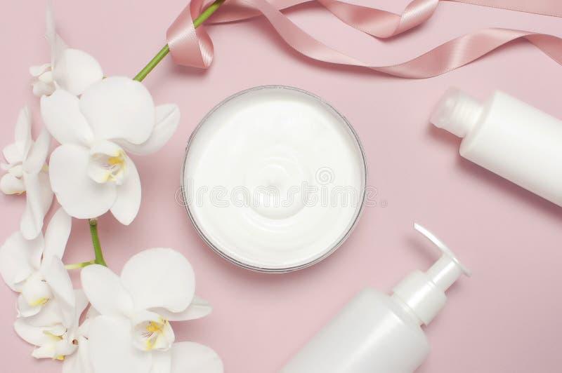 Conceito dos termas da beleza Recipiente aberto com creme, recipientes cosméticos da garrafa, flores brancas da orquídea do Phala imagem de stock royalty free