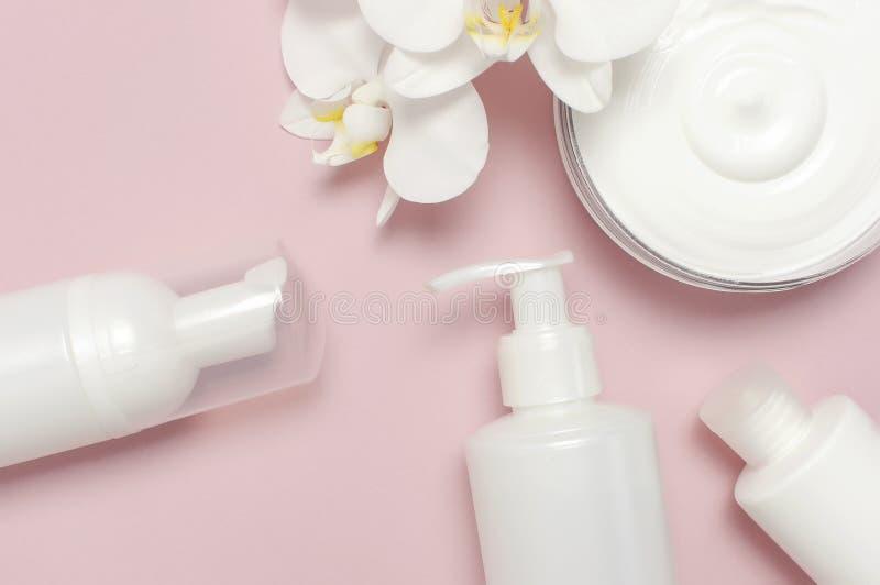Conceito dos termas da beleza Recipiente aberto com creme, recipientes cosméticos da garrafa, flores brancas da orquídea do Phala imagens de stock royalty free