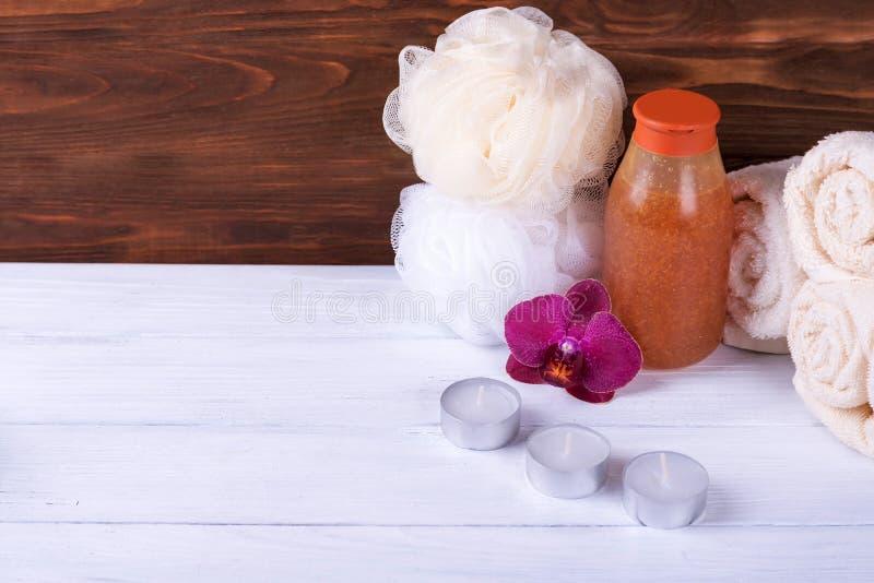 Conceito dos termas Na orquídea de madeira branca do fundo, as toalhas, esponja do banho, esfregam e velas Com espaço da cópia imagem de stock