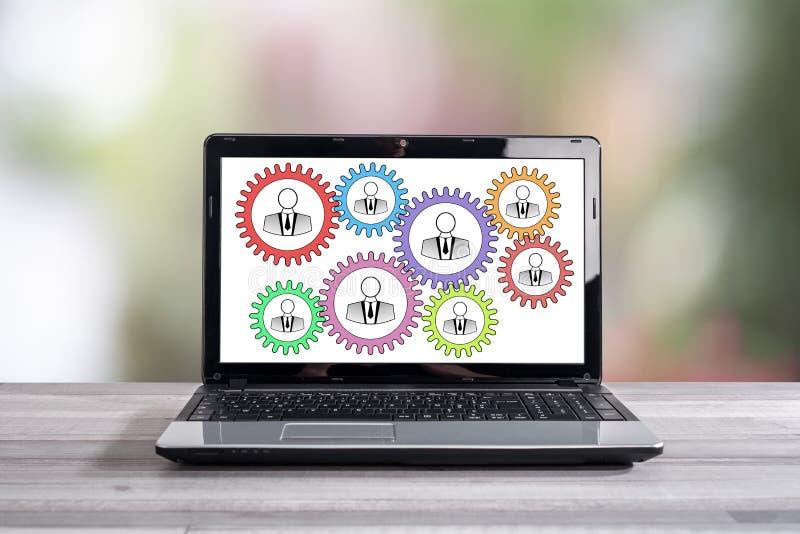 Conceito dos trabalhos de equipa em uma tela do portátil imagem de stock royalty free