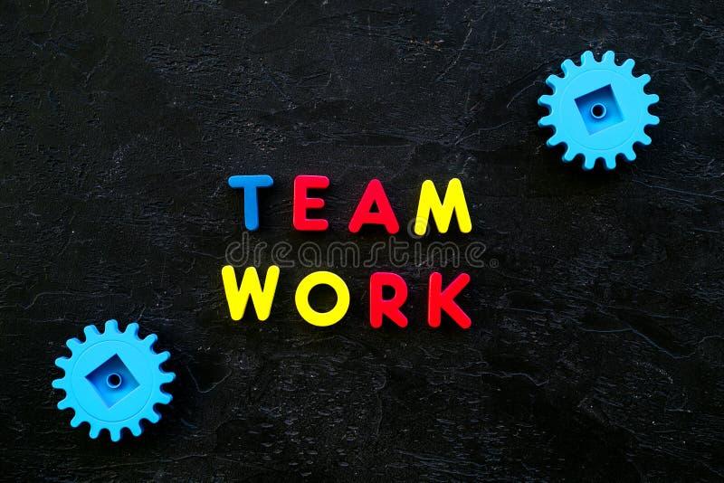Conceito dos trabalhos de equipa Os trabalhos de equipe do texto alinharam com letras coloridas perto das engrenagens do brinqued imagens de stock royalty free