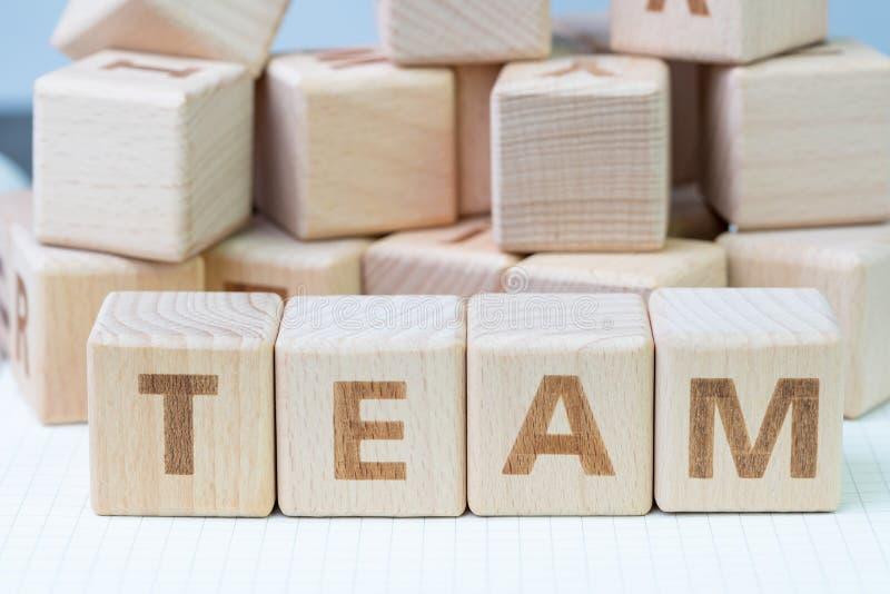 Conceito dos trabalhos de equipe, bloco de madeira do cubo com as letras que formam a palavra EQUIPE no caderno branco do gridlin imagens de stock