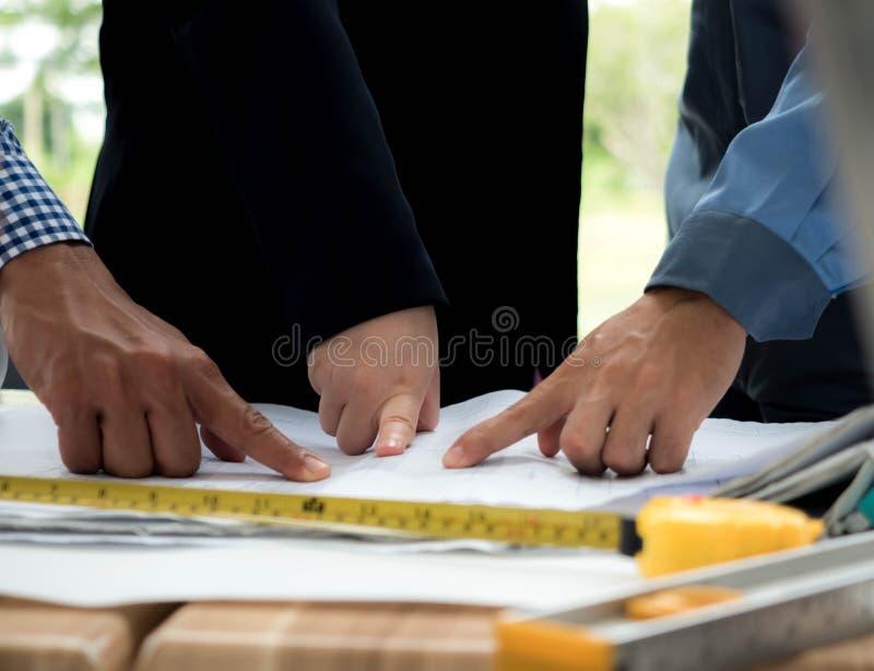 Conceito dos trabalhos de equipe, mãos da reunião do coordenador do arquiteto para o projeto arquitetónico trabalho com sócio e m fotos de stock royalty free