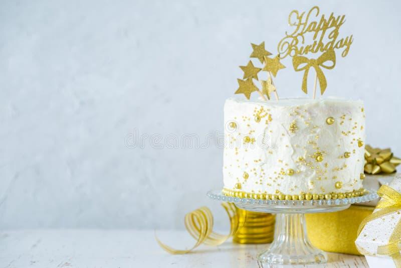 Conceito dourado do aniversário - bolo, presentes, decorações imagem de stock