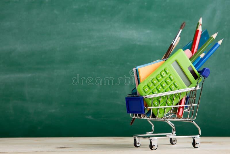 Conceito educativo - material escolar num carrinho de compras na secretária do auditório, fundo de quadros foto de stock royalty free