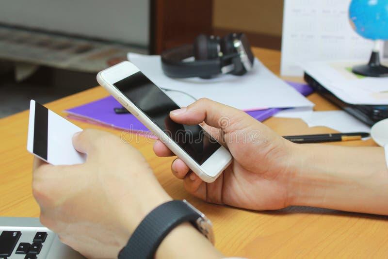 Conceito em linha da compra Homem que usa o cartão esperto móvel do telefone e de crédito na tabela no escritório fotografia de stock