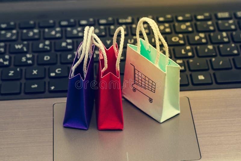 Conceito em linha da compra, três sacos de compras de papel coloridos no teclado do caderno O comércio eletrônico é a compra dos  fotos de stock