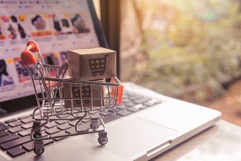 Conceito em linha de compra - caixas do pacote ou de papel com um logotipo do carrinho de compras em um trole em um teclado do po imagem de stock