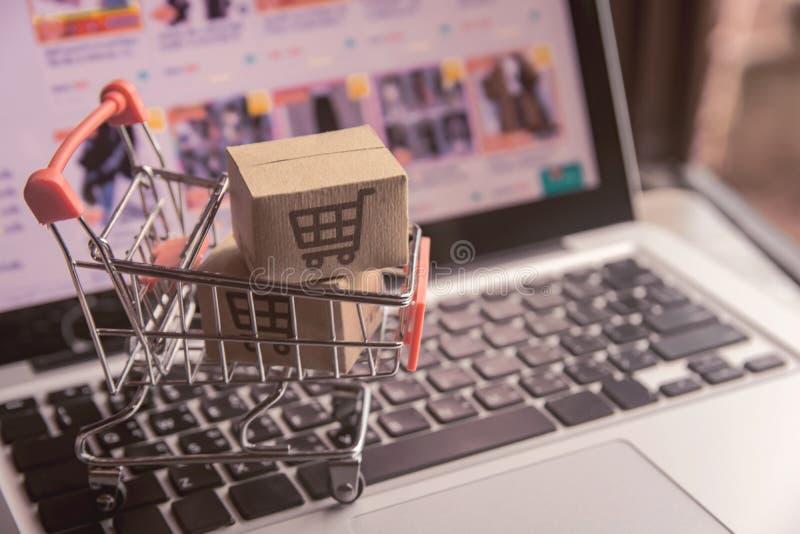 Conceito em linha de compra - caixas do pacote ou de papel com um logotipo do carrinho de compras em um trole em um teclado do po foto de stock