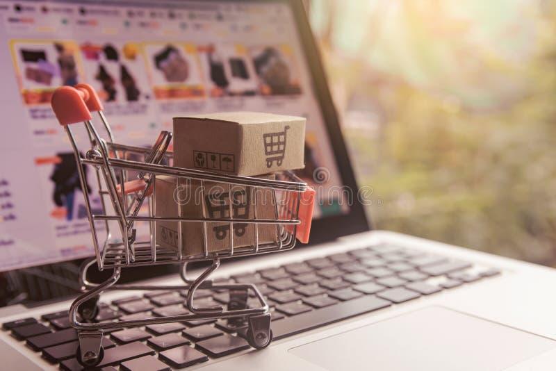 Conceito em linha de compra - caixas do pacote ou de papel com um logotipo do carrinho de compras em um trole em um teclado do po fotografia de stock