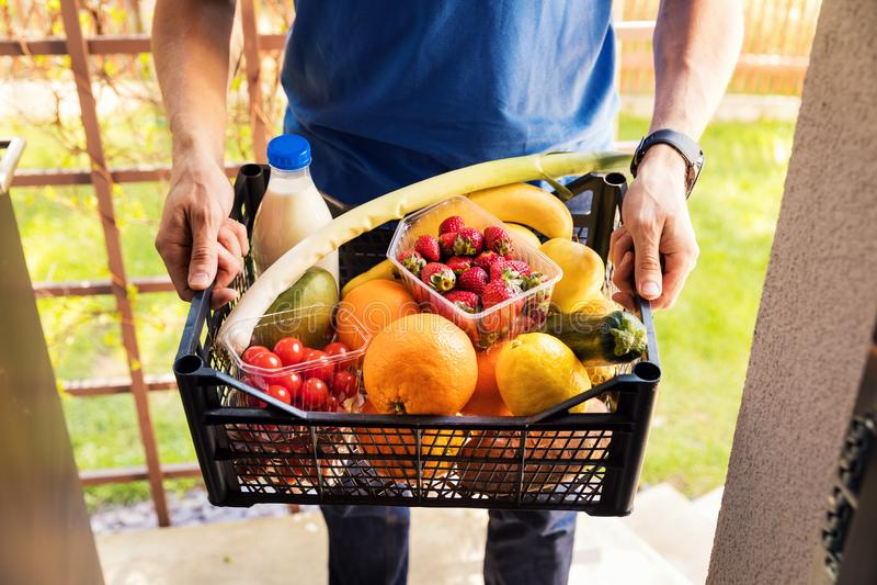 Conceito em linha do serviço das compras na mercearia - homem de entrega com alimento imagens de stock