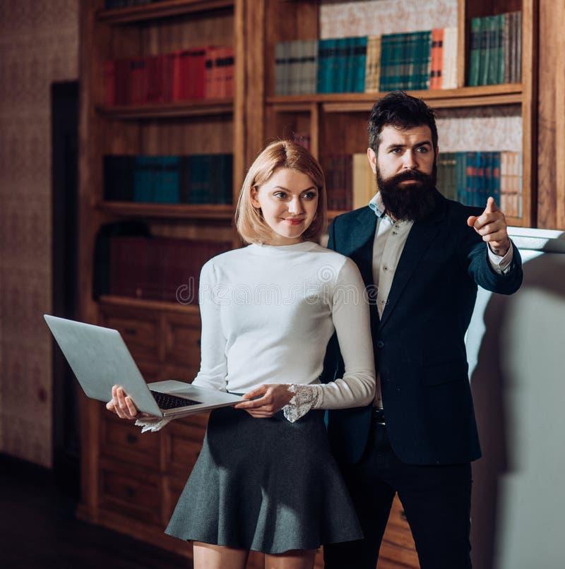 Conceito em linha O homem farpado e a mulher sensual usam a biblioteca digital em linha no portátil Educação em linha da universi foto de stock royalty free